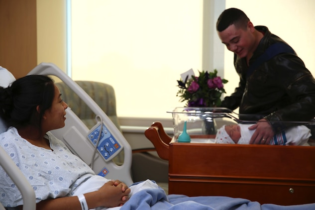 One of the first patients at Camp Pendleton's newest hospital, Lance Cpl. Lucia Y. Cabral, watches her husband, Pfc. Nicholas M. Cabral, marvel at their newborn baby. The Naval Hospital Camp Pendleton facility, built in 1969, was officially decommissioned, requiring patients to be relocated to Pendleton's recently built, 500,000-square foot, replacement hospital Dec. 14. The four-floor building cost $456 million and took more than three years to construct. Lucia is a maintenance management specialist and Nicholas is a warehouse clerk with1st Marine Logistics Group.