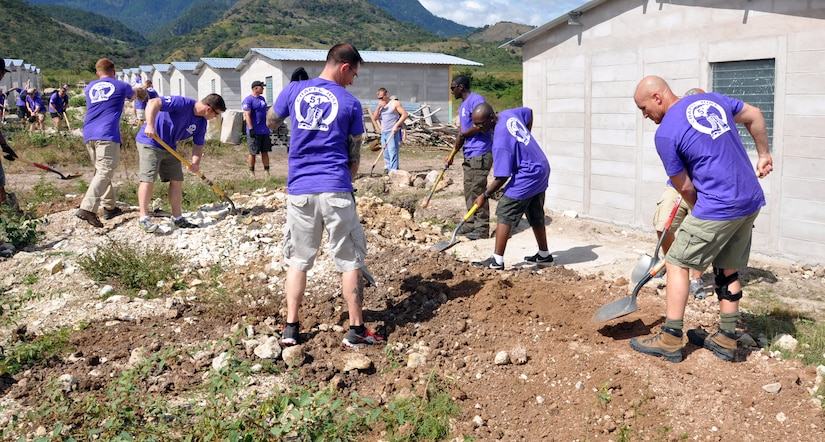 Members of Joint Task Force-Bravo work on clearing and leveling ground for housing in the village of Ajuterique in the Department of Comayagua, Honduras, during the 51st Joint Task Force-Bravo chapel hike, Dec. 14, 2013.  The Task Force members hiked three miles to the village to deliver more than 100 packs of food to families in the community, and then spent the remainder of their time working on a housing project in Ajuterique, doing manual labor to help build homes for families.  (U.S. Air Force photo by Capt. Zach Anderson)