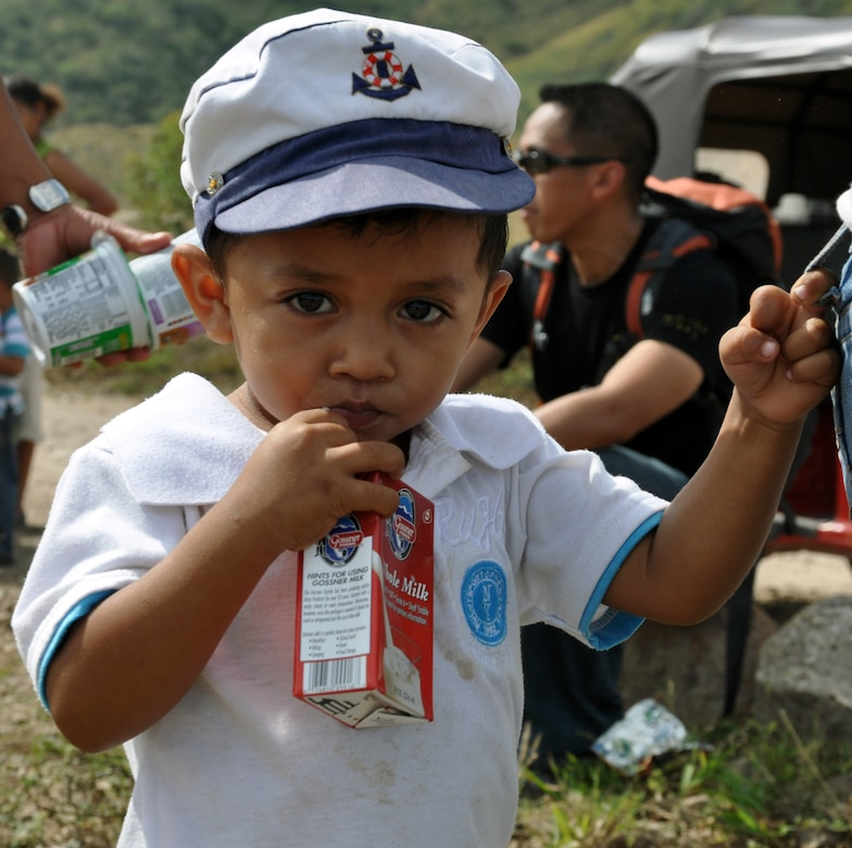 A young Honduran boy enjoys milk that was delivered by members of Joint Task Force-Bravo during the 51st JTF-Bravo Chapel Hike, Dec. 14, 2013.  Members of Joint Task Force-Bravo hiked three-miles to the village of Ajuterique in the Department of Comayagua, Honduras, to deliver more than 100 packs of food to families in need..  The Task Force members then spent the remainder of their time working on a housing project in Ajuterique, doing manual labor to help build homes for families.  (U.S. Air Force photo by Capt. Zach Anderson)