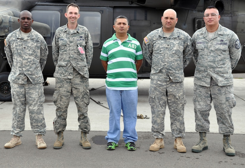 U.S. Army Staff Sgt. Willie Price, U.S. Air Force Capt. Allen Bear, Jose Adalberto Mejia, U.S. Army Staff Sgt. John Fowler, and U.S. Air Force Master Sgt. Michael Batres were recognized for their actions in assisting at the scene of a vehicle accident, Soto Cano Air Base, Honduras, Dec. 16, 2013.  On the evening of Dec. 11, 2013, Adalberto Mejia was driving a taxi with the four service members riding as passengers when the men witnessed a vehicle striking a cow that had wandered onto the road. The vehicle flipped upside down and came to rest in a ditch. The five men came to the aid of the driver of the overturned vehicle, pulling him from the wreckage and then loading him into the taxi to transport him to receive medical treatment. (U.S. Air Force photo by Capt. Zach Anderson)