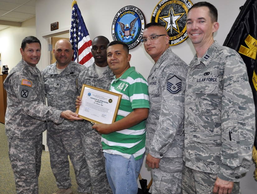 Lt. Col. Alan McKewan, Commander of Joint Task Force-Bravo's Army Forces Battalion, presents a certificate of appreciation to Jose Adalberto Mejia for his actions in helping to assist at the scene of a vehicle accident, Soto Cano Air Base, Honduras, Dec. 16, 2013. On the evening of Dec. 11, 2013, Adalberto Mejia was driving a taxi with U.S. Air Force Capt. Allen Bear, U.S. Air Force Master Sgt. Michael Batres, U.S. Army Staff Sgt. John Fowler and U.S. Army Sgt. Willie Price (pictured) riding as passengers when the men witnessed a vehicle striking a cow that had wandered onto the road. The vehicle flipped upside down and came to rest in a ditch. The five men came to the aid of the driver of the overturned vehicle, pulling him from the wreckage and then loading him into the taxi to transport him to receive medical treatment. (U.S. Air Force photo by Capt. Zach Anderson)