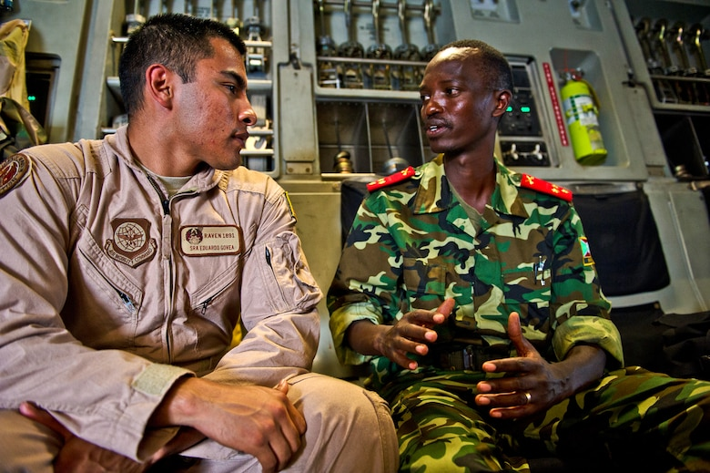 Senior Airman Edurado Govea, a Security Forces Phoenix Raven, speaks with a Burundi soldier before take off in a C-17 Globemaster Dec. 13, 2013 at Bujmumbura Airport, Burundi. In coordination with the French military and African Union, the U.S. military provided airlift support to transport Burundi soldiers, food and supplies in the Central African Republic. This support is aimed at enabling African forces to deploy promptly to prevent further spread of sectarian violence and restore security in CAR. (U.S. Air Force photo/Staff Sgt. Erik Cardenas)