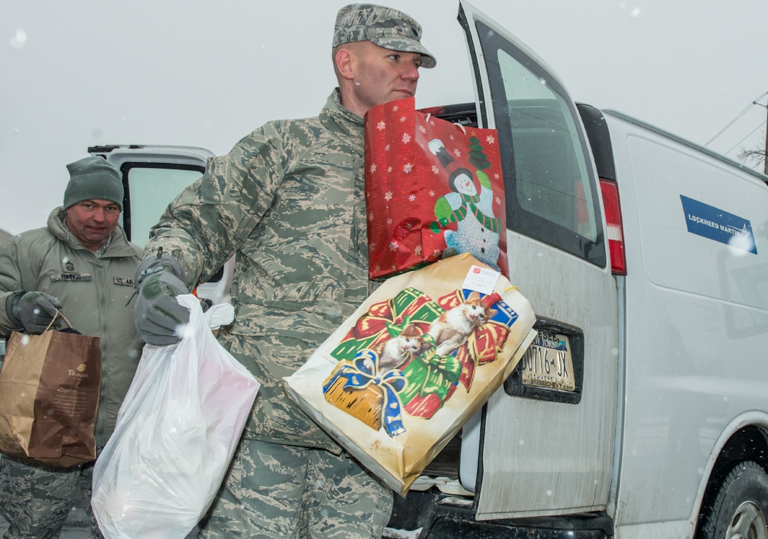Chief Master Sgt. Russell Youngs (Left), Command Chief Master Sergeant of the 174th Attack Wing and Lt. Col. Edward Cook (Right), Commander of the 174th Logistics Readiness Squadron, carry gifts that were received at Shoppingtown Mall on 13 December 2013. The gifts will be distributed downtown at the Oncenter through American Red Cross on 23 December 2013.