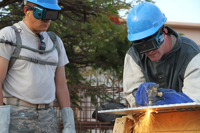 TSgt. Jared Webb looks on as SSgt. Merrell Brown cuts galvanized steel to use as a cover plate for piping at the Space Surveillance Network radar site in Exmouth, Western Australia. (Utah Air National Guard photo by CMSgt. Mark Savage/RELEASED)
