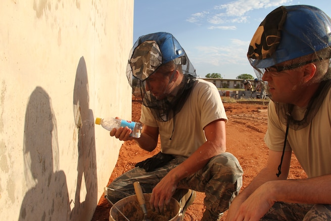 SSgt. Josh David and SSgt. Nathan Jones apply a mortar patch to finish walls on the CBAN radar platform while on a volunteer Deployment for Training in Exmouth, Western Australia. (Utah Air National Guard photo by CMSgt Mark Savage/RELEASED)
