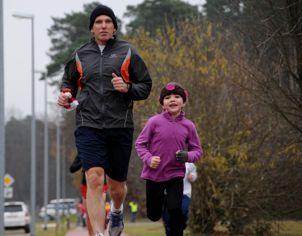 Sarah Langridge (right), 6-years-old, the daughter of Lt. Col. Brian Langridge (left), 86th Operations Group deputy commander, runs toward the finish line of the Jingle Bell Toy Trot 5K at Ramstein Air Base, Germany, Dec. 12, 2013. Sarah said she likes the holiday season and enjoyed running in the 5K. She finished the 3.1 mile race in 32 minutes and 56 seconds. (U.S. Air Force Photo by Tech. Sgt. James M. Hodgman)