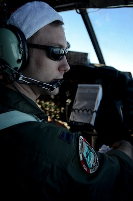 Capt. Michael Kelly looks out the window from the flight deck of the aircraft while flying over the Pacific Ocean during an Operation Christmas Drop mission, Dec. 11, 2013. This year marks the 62nd year of Operation Christmas Drop, which began in 1952, making it the world's longest running airdrop mission. Kelly is a 36th Airlift Squadron C-130 Hercules pilot from Yokota Air Base, Japan. (U.S. Air Force photo/Senior Airman Marianique Santos)