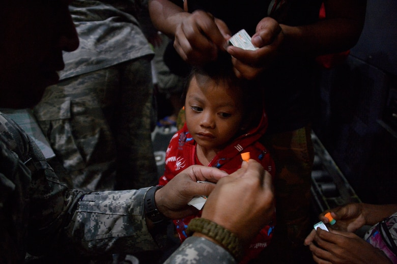 A little girl watches as her father puts on hearing protection after boarding an MC-130 Combat Talon II from 1st Special Operation Squadron Nov. 20. Families in the Philippines affected by Typhoon Haiyan were airlifted from Ormoc to Manila as part of Operation Damayan. (U.S. Navy photo by Mass Communication Specialist 2nd Class Daniel M. Young/Released)