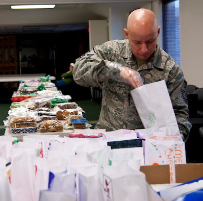 Master Sgt. Tim Allison, 19th Special Operations Squadron first sergeant, unfolds bags during the Commando Cookie Drop at the chapel on Hurlburt Field, Fla., Dec. 16, 2013. First sergeants will deliver bags of cookies to Airmen living in the dorms. (U.S. Air Force photo/Senior Airman Michelle Vickers)