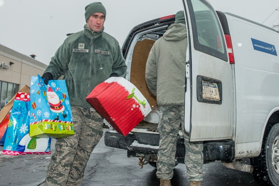 Senior Airman Andrew McNamara of The Eastern Air Defense Sector, helps carry gifts that were received at Shoppingtown Mall on 13 December 2013. The gifts will be distributed downtown at the Oncenter through American Red Cross on 23 December 2013.