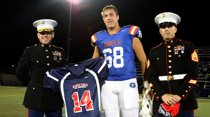 Maj. Brian Donlon, left, the commanding officer of Recruiting Station San Diego, and Staff Sgt. Jeffery Schoebal, right, a recruiter from Recruiting Sub Station North Las Vegas, present Nick Gates, center, with a jersey for the 2014 Semper Fidelis All-American Bowl moments before the kick-off of a football game at Bishop Gorman High School in Las Vegas, Nev., Nov. 15. Gates is one of three players from the RS San Diego area participating in the SFAAB. He will be playing the position of wide receiver for the West Coast team, Jan. 5, 2014 at the StubHub Center in Los Angeles.