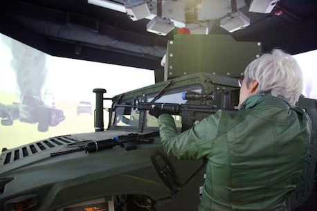 A tour participant takes aim at simulated targets on the 360-degree video screen in the combat convoy simulator at Camp Wilson.