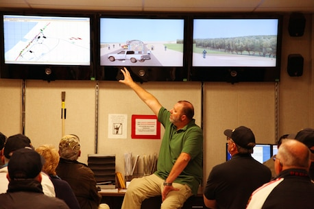 Tour guide Michael King explains to tour participants how instructors create combat convoy scenarios at the Battle Simulation Center at Camp Wilson.