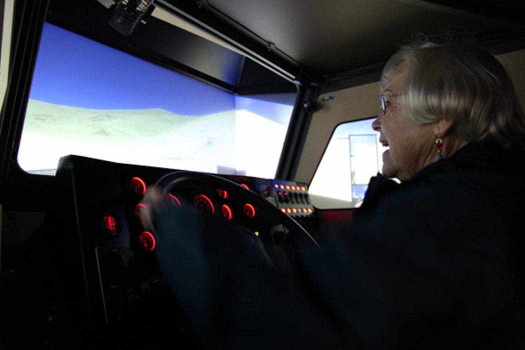 A tour participant gets a feel for being behind the while of a large tactical vehicle during a visit to the driving simulator at the Battle Simulation Center at Camp Wilson.