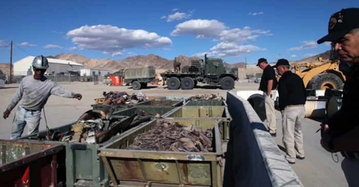 Jay Jones, left, work leader at the Range Sustainment Branch, show members of the High Desert Marines organization of the Victor Valley some of the items collected from Combat Center training ranges and processed at the facility during the group's tour of the installation Nov. 20, 2013. Behind them, Marines offload items collected after an exercise. (Official USMC photo by Kelly O'Sullivan/Released)
