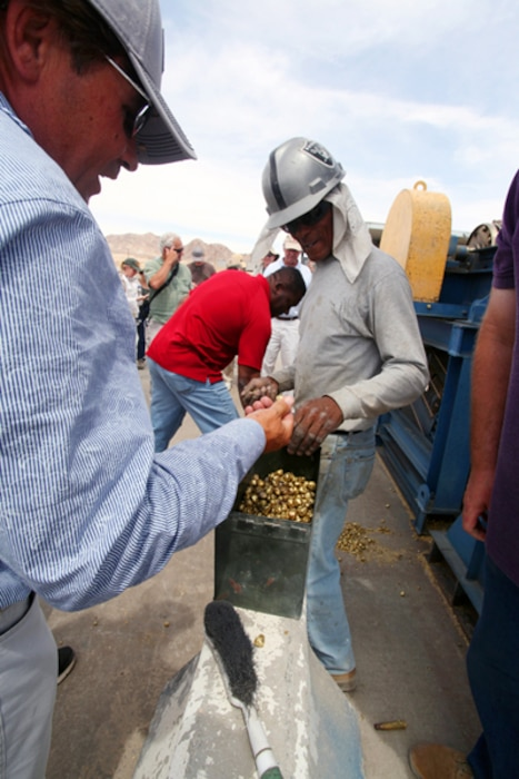 Jay Jones, right,  work leader at the Combat Center's Range Sustainment Branch, shows a tour participant the pellets that result when brass casings are processed at the recycling facility.