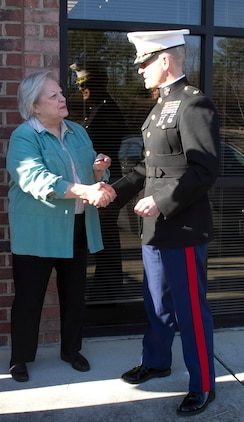 Marine Corps Maj. Brandon J. Gorman, the commanding officer of Marine Corps Recruiting Station Raleigh and Charlotte, N.C., native, presents Vivian Jones, the Mayor of Wake Forest, N.C., with a coin following the Permanent Contact Station Wake Forest grand opening ceremony in Wake Forest, N.C., on Dec. 16, 2013. The Marines held a grand opening featuring a ribbon cutting and Toys for Tots drive to promote the new station. (U.S. Marine Corps photo by Sgt. Dwight A. Henderson/Released)