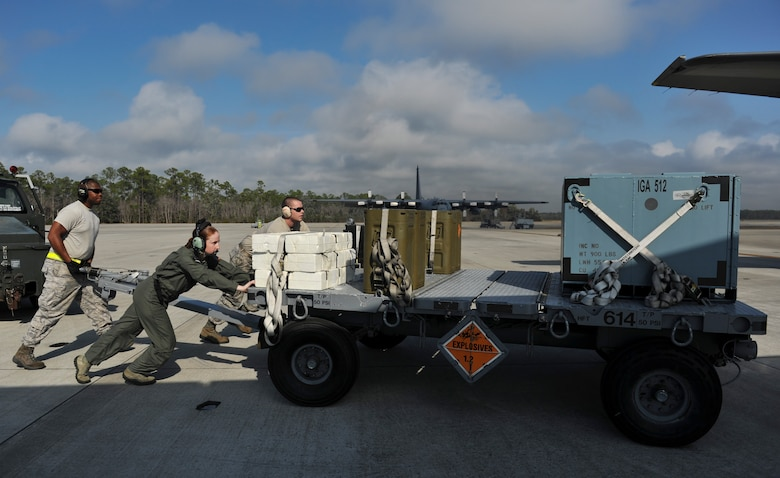 Senior Airmen Patrick Beam and Marcus Montgomery, 1st Special Operations Equipment Maintenance Squadron munitions line delivery drivers, push a munitions trailer with an aircrew member on Hurlburt Field, Fla., Dec. 6, 2013. Line delivery drivers handed 105mm rounds to aircrew members individually through a side door on the aircraft. (U.S. Air Force photo/Staff Sgt. John Bainter)