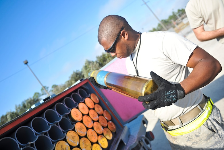 Senior Airman Marcus Montgomery, 1st Special Operations Equipment Maintenance Squadron munitions line delivery driver, inspects a 105mm round on Hurlburt Field, Fla., Dec. 6, 2013. Montgomery inspected each round and transported them to an aircraft once they were deemed undamaged and safe to load. (U.S. Air Force photo/Staff Sgt. John Bainter)