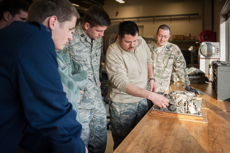 Tech. Sgt. Chuck Rodgers, an engine mechanic from the 123rd Maintenance Squadron, demonstrates the operation of a C-130 turboprop valve housing to a group of U.S. Air Force Reserve Officer Training Corps cadets from the University of Louisville during a tour of the Kentucky Air National Guard Base in Louisville, Ky., Nov. 19, 2013. Valve housings vary the pitch of aircraft propeller blades based on throttle input, controlling whether an aircraft moves forward or backward. (U.S. Air National Guard photo by Maj. Dale Greer)