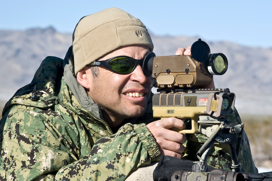 U.S. Navy Chief Petty Officer Carlos Vargas, Naval Special Warfare combatant crewman, bore sights an LA-10u/PEQ handheld laser marker during a Handheld Laser Marker Tactics Development and Evaluation project Dec. 10, 2013, at the Nevada Test and Training Range. The handheld laser marker is a small, lightweight device that emits NATO Band I/II compatible coded laser energy to quickly mark and handoff targets for engagement with precision guided munitions. (U.S. Air Force photo by Senior Airman Matthew Lancaster)