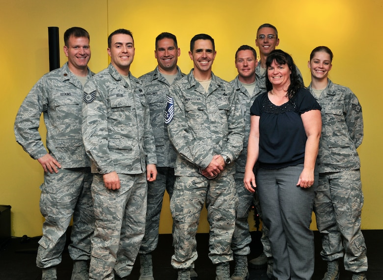 Senior Master Sgt. Benjamin Higginbotham, Aerospace Data Facility-Colorado, poses with his unit members Dec. 13, 2013, at Panther Den on Buckley Air Force Base, Colo. Higginbotham was a part of the December supplemental promotion release for chief master sergeant . (U.S. Air Force photo by Airman 1st Class Samantha Saulsbury/Released)