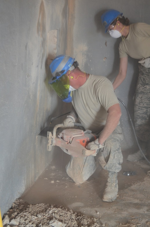 Master Sgt. Randy Frantz, a native of Troy Ill. and a member of 126th Civil Engineer Squadron attached to the 126th Air Refueling Wing, cuts a hole in a concrete wall to make a door way, while Capt. Allyson Benko, a native of Fairview Heights, also a member of the 126th Civil Engineer Squadron, sprays water on it to keep down the dust at Holt Naval Communication Station, Western Australia Aug. 28, 2013. The new door way is part of Operation C-Band Radar And Pedestal NCS NE Holt- Western Australia. (Air National Guard photo by Airman 1st Class Elise Stout)