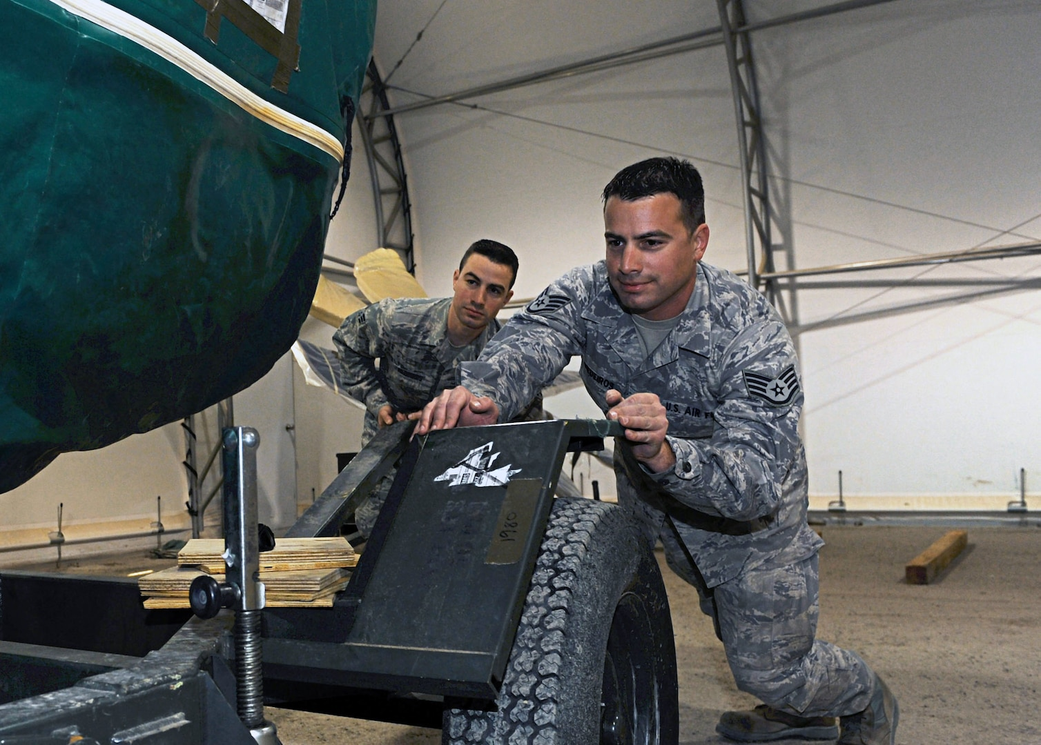 Twin brothers Air Force Staff Sgt. William Medeiros, right, and Air Force Senior Airman Barrington prepare a spare engine for a C-130J in Southeast Asia, Dec. 11, 2013. The Rhode Island Air National Guardsmen serve together with the 386th Expeditionary Aircraft Maintenance Squadron.