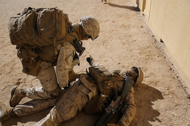 Corporal Phillip Jacoby, team leader, Bravo Company, 1st Battalion, 7th Marine Regiment, and a native of Kalamazoo, Mich., treats a simulated casualty during a counterinsurgency exercise on Range 220 at Marine Corps Air Ground Combat Center Twentynine Palms, Calif., Dec. 9, 2013. The $140 million urban warfare training facility consists of more than 1,000 buildings and is divided into four sectors. The buildings replicate what can be found in an urban town to include gas stations, factories, one story complexes, marketplaces and multiple story buildings. The battalion is slated to continue a vigorous training schedule before deploying to Afghanistan this spring.