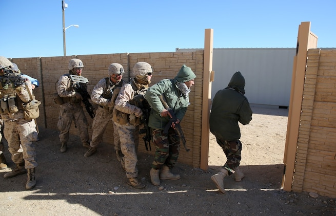 Marines with Bravo Company, 1st Battalion, 7th Marine Regiment, follow Afghan role-players into a compound during a counterinsurgency exercise on Range 220 at Marine Corps Air Ground Combat Center Twentynine Palms, Calif., Dec. 9, 2013. The $140 million urban warfare training facility consists of more than 1,000 buildings and is divided into four sectors. The buildings replicate what can be found in an urban town to include gas stations, factories, one story complexes, marketplaces and multiple story buildings.