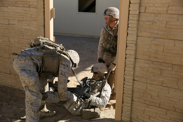 Marines with Bravo Company, 1st Battalion, 7th Marine Regiment, evacuate a simulated casualty during a counterinsurgency exercise on Range 220 at Marine Corps Air Ground Combat Center Twentynine Palms, Calif., Dec. 9, 2013. The $140 million urban warfare training facility consists of more than 1,000 buildings and is divided into four sectors. The buildings replicate what can be found in an urban town to include gas stations, factories, one story complexes, marketplaces and multiple story buildings. The battalion is slated to continue a vigorous training schedule before deploying to Afghanistan this spring.