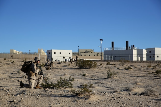 Marines with Bravo Company, 1st Battalion, 7th Marine Regiment, halt during a patrol on Range 220 at Marine Corps Air Ground Combat Center Twentynine Palms, Calif., Dec. 9, 2013. The $140 million urban warfare training facility consists of more than 1,000 buildings and is divided into four sectors. The buildings replicate what can be found in an urban town to include gas stations, factories, one story complexes, marketplaces and multiple story buildings. The battalion is slated to continue a vigorous training schedule before deploying to Afghanistan this spring.