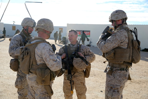 Lieutenant Col. Seth E. Yost, commanding officer, 1st Battalion, 7th Marine Regiment, speaks with company commanders during a counterinsurgency exercise on Range 220 at Marine Corps Air Ground Combat Center Twentynine Palms, Calif., Dec. 9, 2013. The $140 million urban warfare training facility consists of more than 1,000 buildings and is divided into four sectors. The buildings replicate what can be found in an urban town to include gas stations, factories, one story complexes, marketplaces and multiple story buildings. The battalion is slated to continue a vigorous training schedule before deploying to Afghanistan this spring.