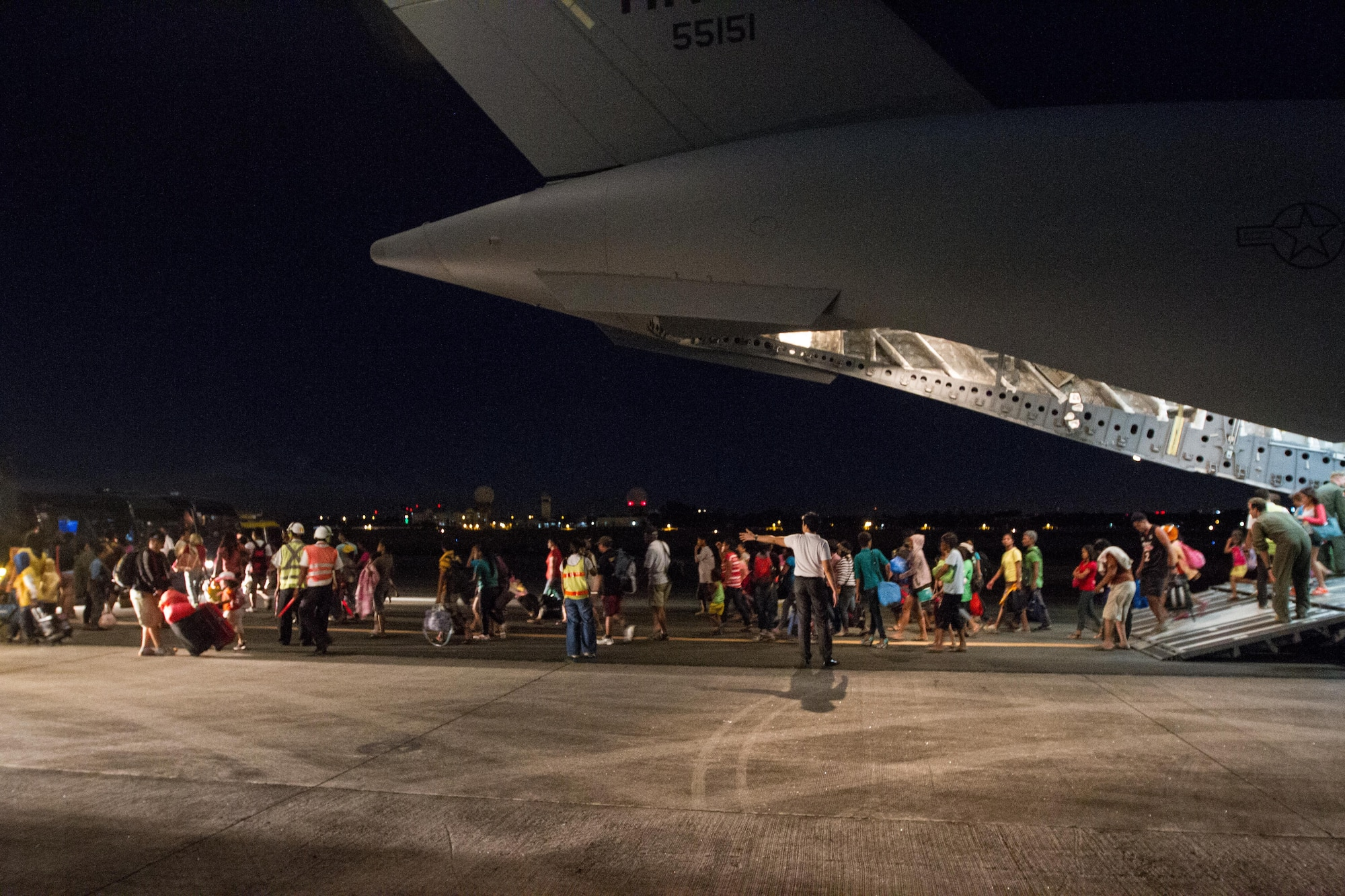 Displaced residents from Tacloban, Philippines, exit a C-17 Globemaster III after being evacuated to Manila Nov. 17, 2013 during Operation Damayan. The aircrew, deployed from Joint Base Pearl Harbor-Hickam, Hawaii, aided in the successful rescue of 1,177 evacuees while flying humanitarian missions in support of humanitarian assistance and disaster relief effort following Super Typhoon Haiyan. The 535th Airlift Squadron C-17 is one of two deployed to the region. (U.S. Air Force Photo/Staff Sgt. Ramon Brockington)