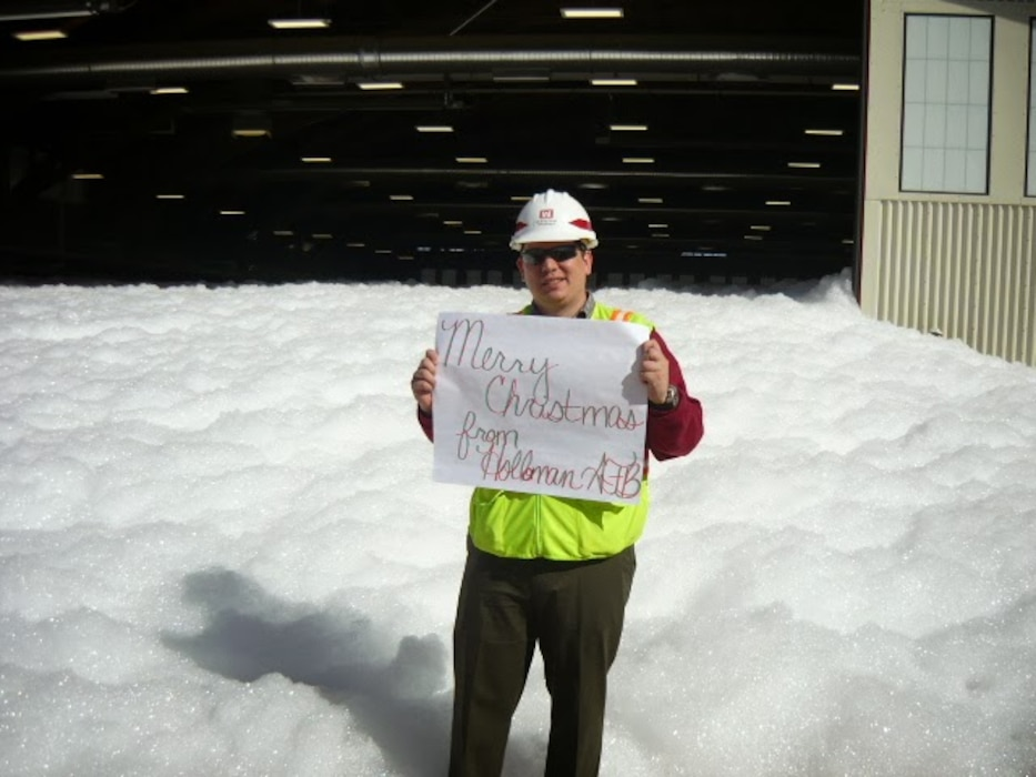 """A Corps employee holds a sign that reads ""Merry Christmas from Holloman AFB"" outside a hangar where a foam dump test was performed."" Photo by Daniel Garcia."