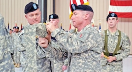 Lt. Col. Robert E. Lee Magee, commander, 1st Bn., 18th Inf. Regt., left, and Command Sgt. Maj. Clinton Reiss, 1st Bn., 18th Inf. Regt., right, furl their unit colors during a Dec. 3 color-casing ceremony at Marshall Army Airfield.  Photo by: Sgt. Daniel Stoutamire, 2ND ABCT.