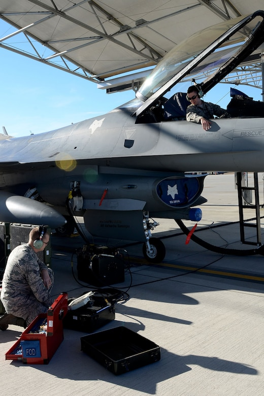 U.S. Air Force Senior Airmen Robert Tucker (left) and Earl Sale, with the 495th Fighter Group, Det. 157, 169th Aircraft Maintenance Squadron avionics shop at McEntire Joint National Guard Base, South Carolina Air National Guard, set up the Joint Service Electronic Combat Systems Tester to an F-16 Fighting Falcon, Dec. 11, 2013. The JSECST is a 180-day preventative maintenance practice that performs a confidence test of the radar threat warning system in the jet.  (U.S. Air National Guard photo by Tech. Sgt. Caycee Watson/Released)