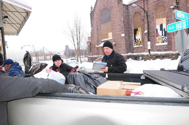 Master Sgt. Melissa Shenefiel and Master Sgt. Kenneth Devole unload the donated clothing for the Western New York Veterans Housing Coalition in Buffalo, NY. on Dec. 18, 2013 (New York Air National Guard photo/Senior Master Sgt. Ray Lloyd)