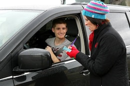 Kristyn Fleming gives Petty Officer 3rd Class Brice Courtnage a slip to redeem presents for him family during the Armed Services YMCA's Secret Santa Event Dec. 19. Fleming is an operations assistant with the ASYMCA.