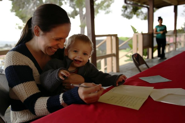 Victoria Courtnage and her son, Ben, write a thank you letter to the sponsors who donated gifts to her family during the Armed Services YMCA's Secret Santa Event Dec. 19.