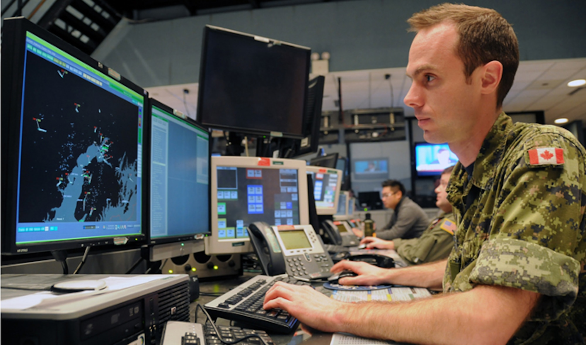 Royal Canadian air force Capt. Dave Gosselin tracks aircraft in Alaska air space ensuring air sovereignty in the Alaskan NORAD Region Regional Air Operations Center. U.S. and Canadian service members utilize 15 radar stations to monitor Santa as he traverses the airspace around the northern latitudes of North America, a mission ANR has successfully accomplished for 50 years. (U.S. Air Force photo/Tech. Sgt. John Gordinier)