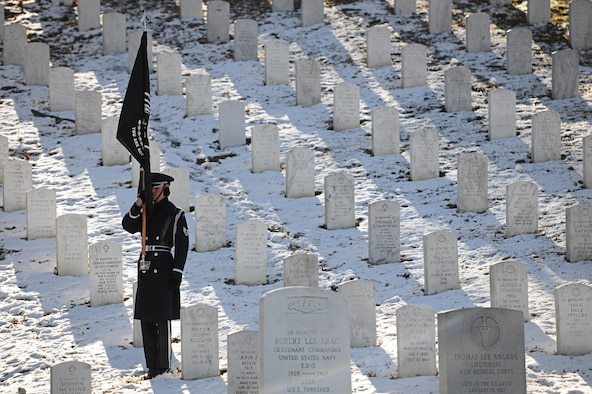 A U.S. Air Force Honor guardsman holds the Prisoner of War Flag during a funeral honoring Col. Francis J. McGouldrick Dec. 13, 2013, at Arlington National Cemetery, Va. McGouldrick was laid to rest after being mission in action for 45 years. McGouldrick's remains were found in a remote jungle in Laos. (U.S. Air Force photo/Airman 1st Class Nesha Humes)