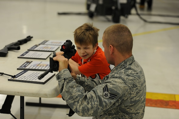 Senior Airman Matthew Caudill assists Zachary Balog, 6, in getting a good sight picture on an M4 rifle Dec. 14, 2013, at the 26th Annual Parents and Children Fighting Cancer Christmas party at Joint Base Andrews, Md. The Fisher House, Andrews, PCFC, and various organizations, donated their time and resources for the event. Caudill is a 11th Wing Security Support Squadron combat arms instructor. (U.S. Air Force photo/Aimee Fujikawa)