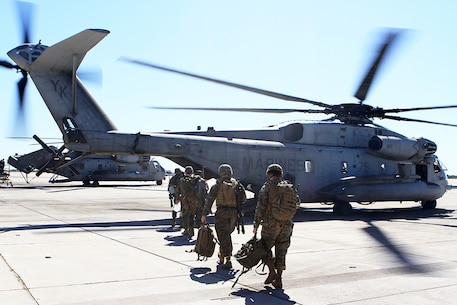 "A helicopter support team prepares to board a CH-53E Super Stallion with Marine Heavy Helicopter Squadron 466, ""Wolfpack,"" 3rd Marine Aircraft Wing, aboard Marine Corps Air Station Miramar, Calif. Feb. 28. The HST will coordinate and oversee the suspension of a load from the underside of the Super Stallion during external lift training."