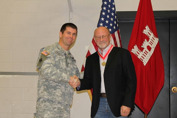 Randy Braley shakes hands with Col. Mark Deschenes, Rock Island District Commander, after being awarded the Order of the de Fleury Medal Dec. 9 for his service and support as the Kabul Area office, Afghanistan resident engineer and for his 32-years as a Corps of Engineers employee.