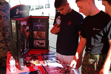 Sgt. Reed, a recruiter with Recruiting Sub Station Palm Desert, explains different Marine Corps enlistment programs during a Toys for Tots event in Palm Desert, Calif., Dec. 8, 2014.