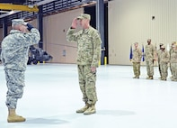 Capt. Aaron Peters, commander, Headquarters and Headquarters Company, 601st Aviation Support Battalion, 1st Combat Aviation Brigade, 1st Infantry Division, right, reports to Col. Frank Muth, 1st Inf. Div. deputy commanding officer for support, left, during a redeployment ceremony Dec. 7 at Marshall Army Airfield.  The Soldiers were part of the trail party portion of Task Force Saber, which returned from Afghanistan in support of Operation Enduring Freedom.