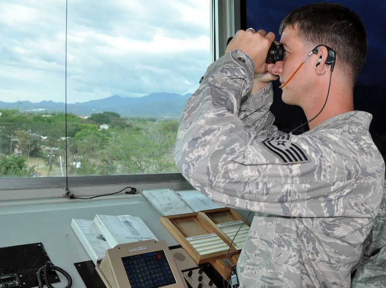 U.S. Air Force Tech. Sgt. Charles Simper, an Air Traffic Control Watch Supervisor assigned to the 612th Air Base Squadron, Joint Task Force Bravo, directs air traffic from the control tower at Soto Cano Air Base, Honduras, Dec. 19, 2013. Air traffic controllers in the tower are responsible for directing air traffic departing and arriving at Soto Cano, as well as vehicle traffic that occurs on the controlled movement area (CMA), which includes the area of the landing zones and runways. (U.S. Air Force photo by Capt. Zach Anderson)