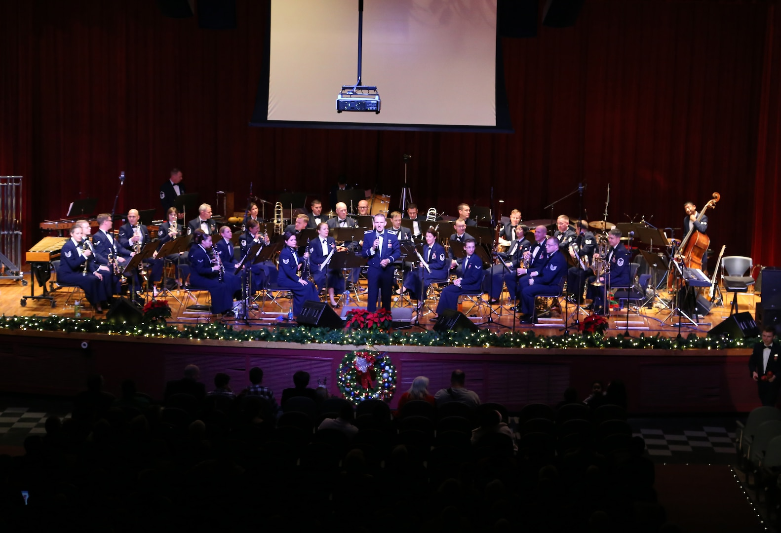 Air Force Capt. Joseph Hansen, Air Force Band of the West deputy commander and conductor, explains the story behind the pieces performed Dec. 17 at the Joint Base San Antonio-Lackland Bob Hope Theater. (U.S. Air Force photo by Airman 1st Class Lincoln Korver)