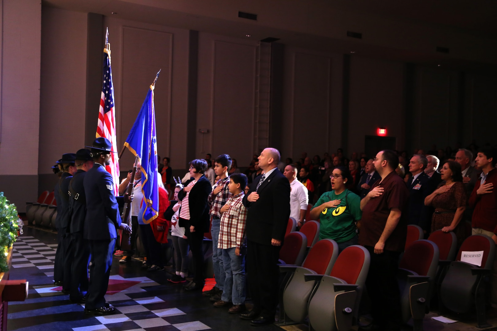 Audience members show respect to the country by placing their hand over their heart or standing at attention while military training instructors present the colors Dec. 17 at the Joint Base San Antonio-Lackland Bob Hope Theater. (U.S. Air Force photo by Airman 1st Class Lincoln Korver)